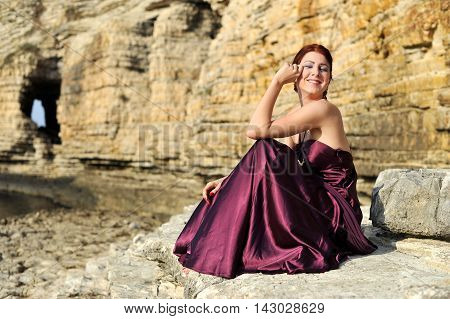 beautiful young elegant women posing on nature with claret red dress