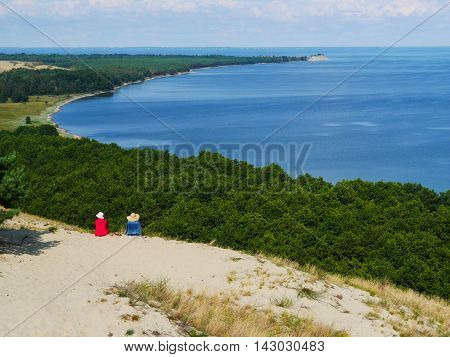 two friends sit on sand dune and meditate over panoramic view of sea and forest