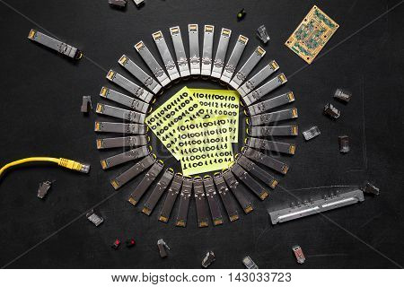 Electrical Internet SFP network modules RJ45 ethernet cable RJ45 connectors circuit board with microchips diodes and yellow stickers of paper with digits (one and zero) are on the black background poster