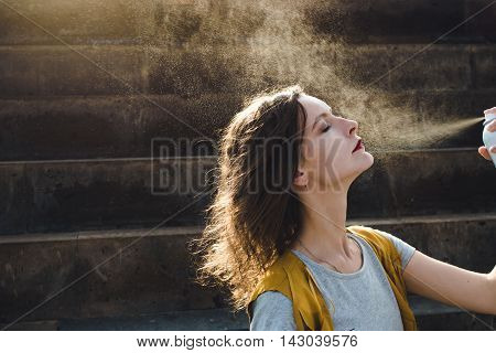 Photo of the Young woman spraying face with thermal water. Enjoying, skin care concept.