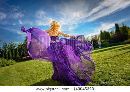 Blonde gorgeous woman in long purple luxurious dress posing in garden. Dress fluttering on wind.