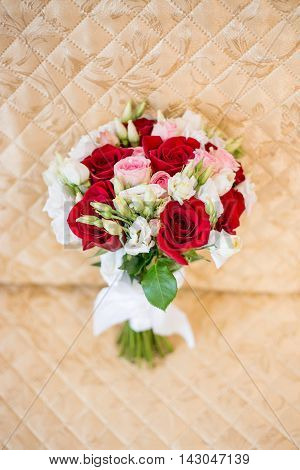 Beautiful classic bridal wedding bouquet with red and white flowers stands on vintage colden chair.