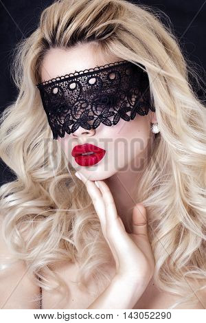 Beautiful Blonde Woman with Black Lace mask over her Eyes. Red Sexy Lips. Open Mouth. Manicure and Makeup. Make up concept. Passion
