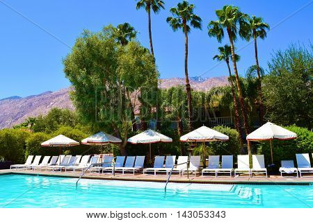 Outdoor poolside furniture including lounge chairs with umbrellas taken in Palm Springs, CA