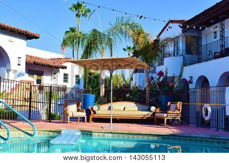 Outdoor furniture including a sofa, chairs, and an umbrella beside a pool taken in a courtyard at a Spanish style hacienda villa