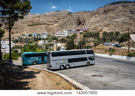 CHORA SFAKION, CRETE, GREECE - JULY 2016: Bus station with parked buses at Chora Sfakion town on Crete island, Greece