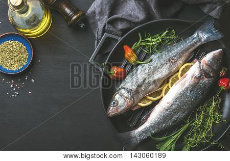 Ingredients for cookig healthy fish dinner. Raw uncooked seabass fish with olive oil, herbs and spices on black grilling iron pan over dark background, top view, copy space, horizontal composition