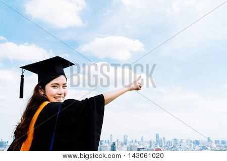 Beautiful asian university or college graduate student woman in graduation academic dress or gown smiling and pointing at copy space on blue sky background education or success concept