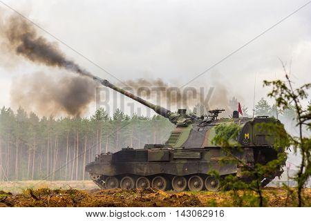 german self-propelled howitzer shoots on a battlefield