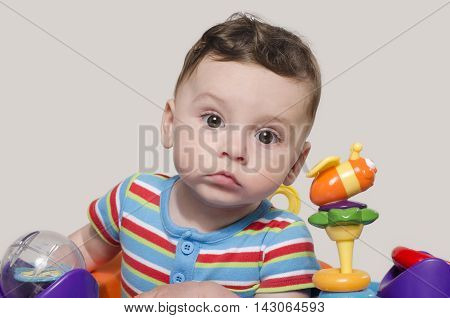 Cute baby boy sitting and playing with toys. Adorable six month old child happy looking curious.