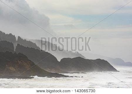 Misty and Foggy Oregon Coast cliffs and forests with stormy sky and ocean waves