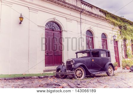 COLONIA DEL SACRAMENTO, URUGUAY - MAY 04, 2016: rustic old car parked in the street next to an ancient house.