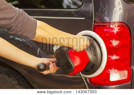 power buffer cleaning the tail lights of a car.