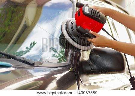 hands holding a polisher while cleanning the door of a car.