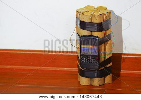 set of explosives conected to a cellphone standing on the ground.