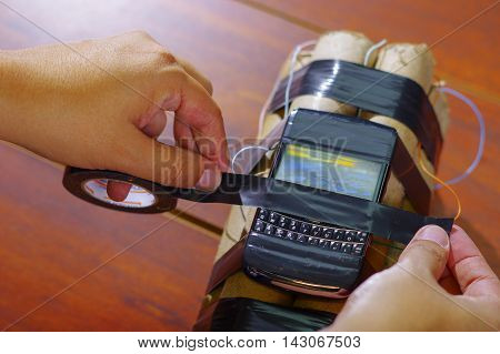 hands tying the caellphone with tape to a set of explosives.
