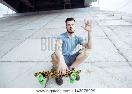 young handsome real hipsrter guy bearded staying under the bridge extreeme with leopard skateboard, lifestyle people concept smiling