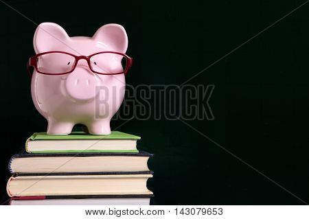 Piggy bank with glasses and blackboard copy space, back to school concept