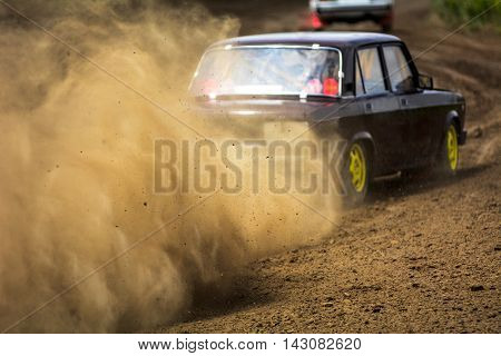 Autocross on a dusty road. Cars in the competition on a winding road