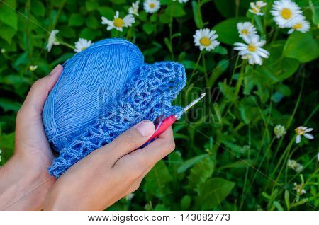 Female Hands Holding Blue Cotton Yarn And Openwork Fabric On A Background Of Green Grass