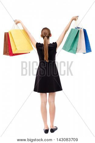 back view of woman with shopping bags. backside view of person.  Rear view people collection. Isolated over white background. Blonde in a short black dress holding aloft shopping bags.