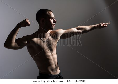 Young man with a naked torso standing in the studio on a gray background. The athlete demonstrates biceps and shows his hand towards