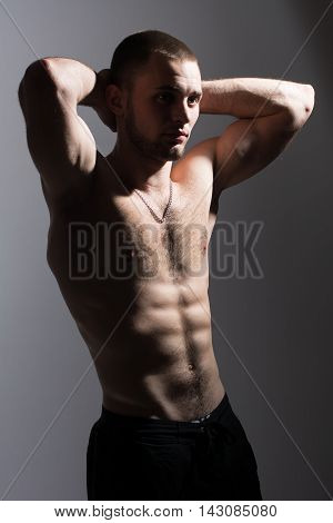 Young man with a naked torso standing in the studio on a gray background. An athlete with a beautiful body