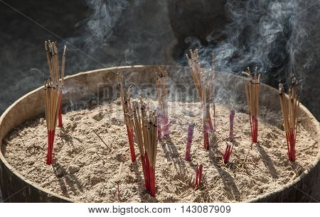 Temple Incense Sticks Showing Smoke Trails And Sand Filled Bowel Used In Buddhist Ceremonies Asia