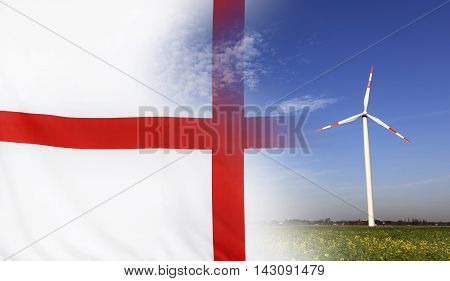 Concept clean energy with flag of England merged with wind turbine in a blue sunny sky and green grass with flowers