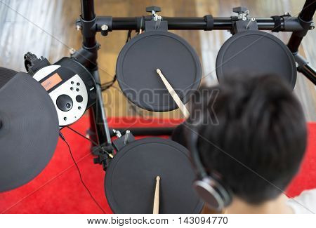Asian boy learning play electronic drum in music room
