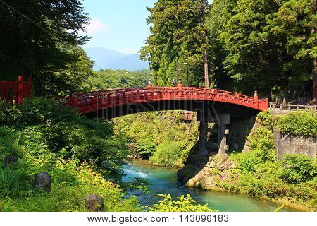 July 2015 at Nikko, Japan. The photo is red shinkyo bridge over the stream with green background of summer