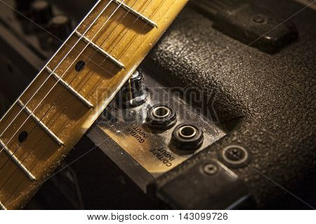 Electric guitar neck over amplifier device. Closeup
