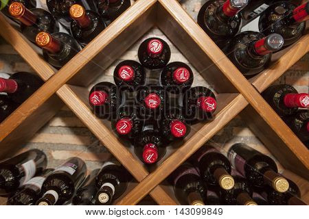 Madrid Spain - July 9 2016: rhomboid wine rack with multiple bottles of spanish red wine lying in restaurant storage