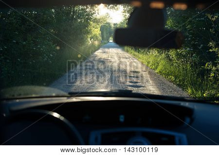 Bumpy dirt road with holes against sunshine in background shot through a windshield. Shallow field of depth.