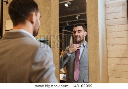 sale, shopping, fashion, style and people concept - happy young man choosing and trying tie on and looking to mirror in mall or clothing store