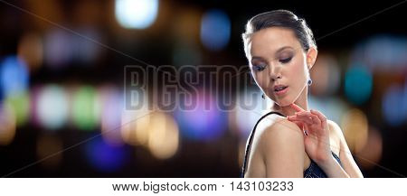 beauty, jewelry, people, nightlife and luxury concept - beautiful young asian woman with earring over night lights background