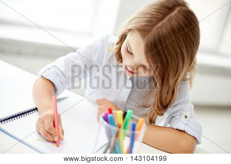 education, creation, art, people and children concept - happy girl drawing with felt-tip pen in notebook
