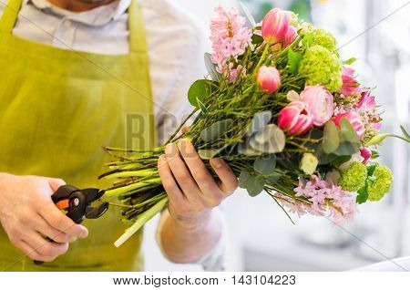 people, business, sale and floristry concept - close up of florist man making bunch and cropping stems by pruner at flower shop