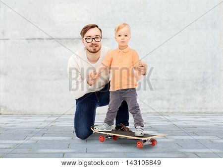 family, childhood, fatherhood, leisure and people concept - happy father and and little son on skateboard over urban street background