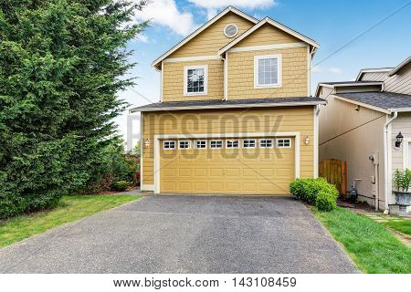Curb Appeal. Yellow Two Level House Exterior With Garage.