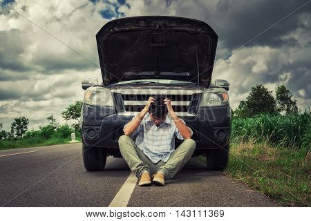 young stressed man having trouble with his broken car looking in frustration on failed engine poster