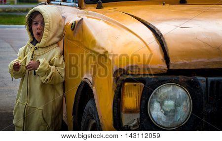 Pensive Little Girl Standing Near An Old Car