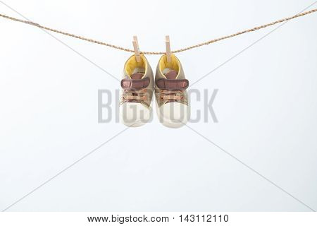 Baby shoes hanging on a rail junction on the white background.