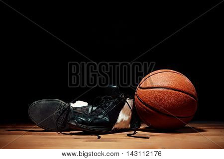 Basketball equipment - ball and basketball sneakers on wooden floor