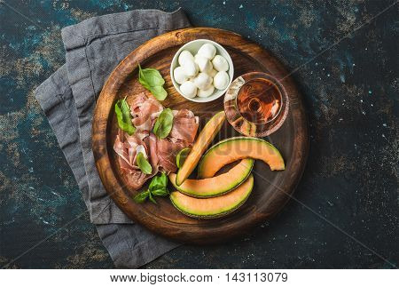 Italian antipasti snack for wine. Prosciutto ham, cantaloupe melon, mozzarella cheese, fresh basil leaves and glass of rose on wooden round serving board over grunge dark plywood background, top view