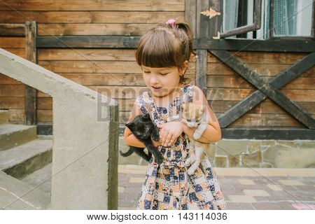 girl playing with kittens on the terrace.