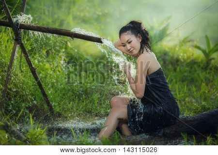 beautiful young woman takes bath naturally flows from the bamboo chute.