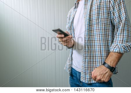 Bored casual man in plaid shirt using mobile phone to waste time