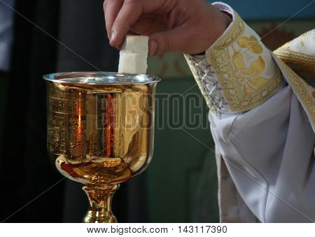Hands of priest consecrates bread during orthodox liturgy ceremony