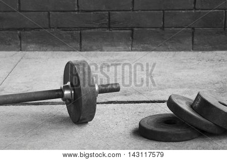 Iron barbell bar in a gym against a brick wall